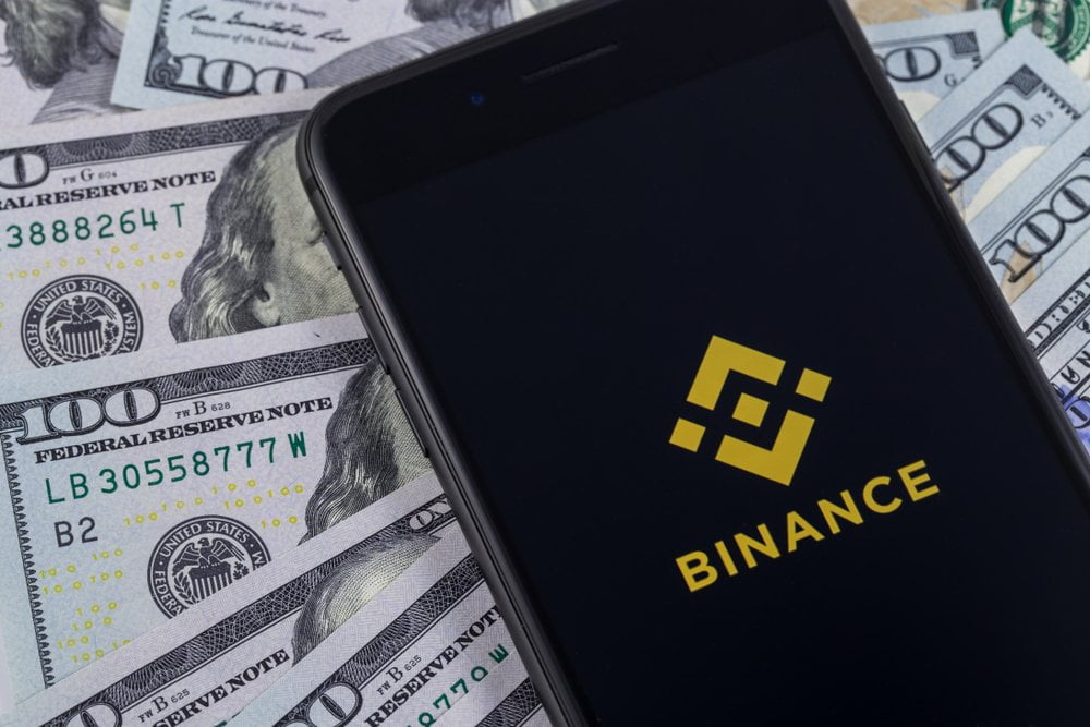 iPhone and Binance logo and dollars